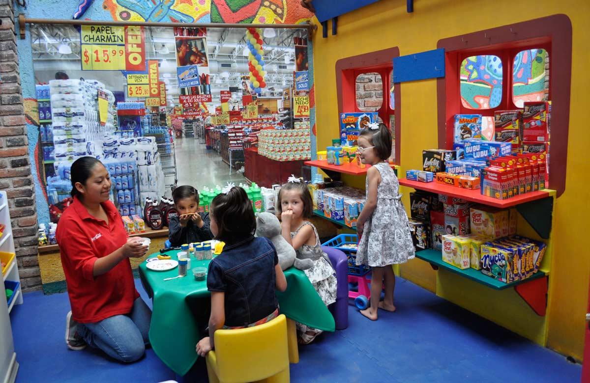 Los niños juegan a ser grandes cobrando y pagando en la caja.